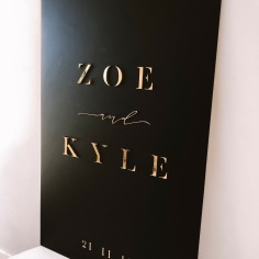 ZOE & KYLE / welcome signage in gold acrylic and matte black acrylic